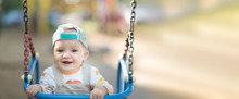Baby Boy In A Cap And Beige Corduroy Jumpsuit Having Fun On A Swing. Copyspace