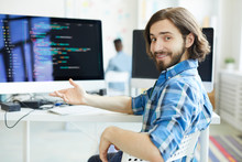 Young Successful Specialist In Data Decoding Sitting By Workplace And Pointing At Computer Monitor