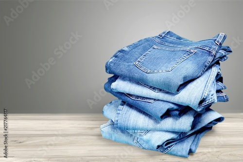 Fotografia  Pile of blue jeans over white background