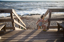 A Child Climbs Down A Beach Stairway.