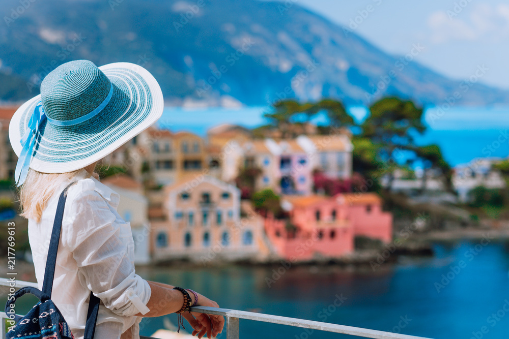 Fototapety, obrazy: Tourist woman in blue sunhat and white clothes enjoying top view of colorful tranquil village Assos on sunny day. Visiting Kefalonia in summer time on Greece travel vacation