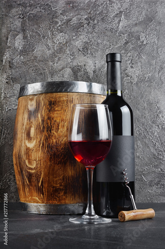 Papiers peints Vignoble Red wine bottle with glass for tasting and wooden barrel in dark cellar