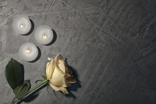 Beautiful White Rose And Candles On Grey Background, Top View. Funeral Symbol