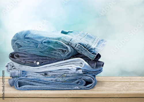 Poster  Pile of blue jeans over white background
