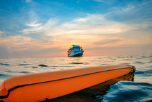 A Surface Marker Buoy And Dive Boat On The Surface Of A Warm Tropical Ocean At Sunset
