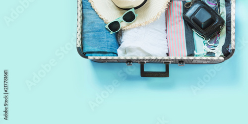 Fototapeta Open suitcase with female clothes for trip on pastel blue. Top view with copy space. Summer concept travel. obraz