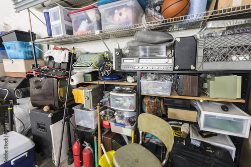 Obraz Full shelves of vintage electronics, boxes and sports equipment in typical suburban garage. - fototapety do salonu