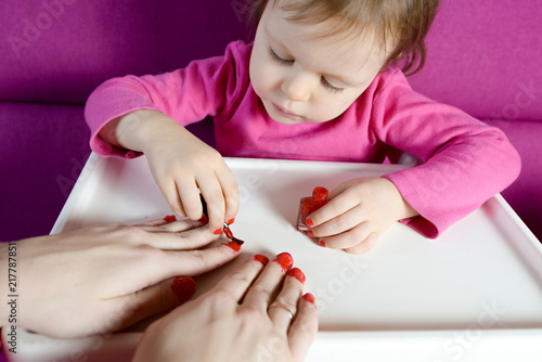 Fotografie, Obraz  The child paints the nails of his mother with varnish
