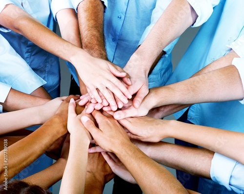 Group of people stacking hands together Wall mural