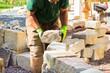 canvas print picture - Mann baut Trockenmauer aus Sandstein