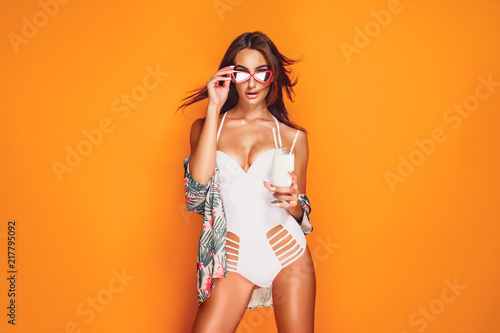 Fotografia Lovely young female in swimwear and sunglasses holding glass of fresh drink whil