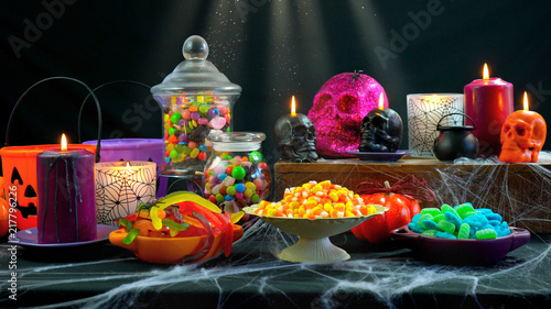 Fényképezés Happy Halloween trick or treat party table with bowls and apothecary jars of candy with skull candles against a black background, scooping candy close up
