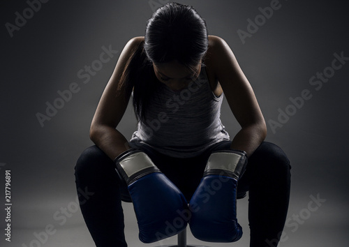 Black female wearing boxing gloves looking angry as a boxer, MMA fighter or self defense trainer sitting after working out.  She is portraying female strength and determination.