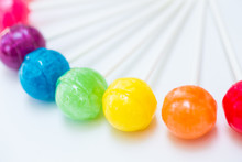 Rainbow Design Of Sweet Colorful Lollipops Against White Background