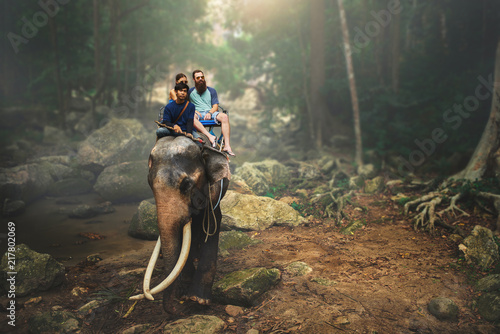 Fotografia  tourist couple riding elephant through thai jungle by river on koh samui thailan