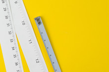 White Measuring Tapes With Centimetre And Inches On Vivid Yellow Background With Copy Space, Length, Long Or Maker Concept
