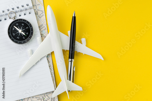 Flat lay or top view of black pen, miniature airplane, compass, notepad and map on vivid yellow background table with blank copy space, tourist, vacation or travel destination plan concept