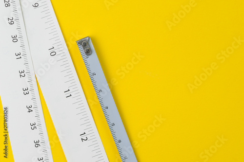 White measuring tapes with centimetre and inches on vivid yellow background with Fototapet