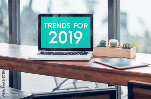 Fotografía  Trends for 2019 word in laptop computer screen with tablet on wood stood table in at window with blur background,Digital Business or marketing trending