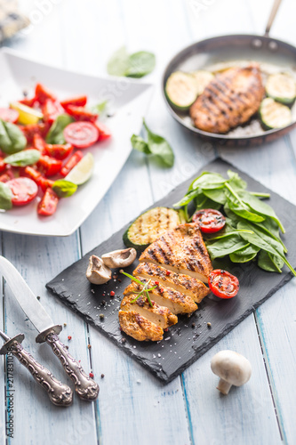 Grilled chicken breast on slate board.