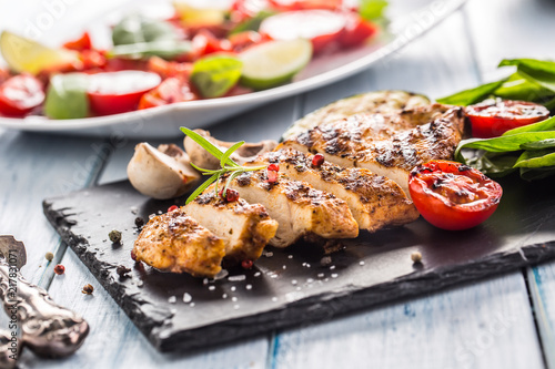 Grilled chicken breast on slate board.