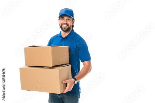 Obraz handsome happy young delivery man holding cardboard boxes and smiling at camera isolated on white - fototapety do salonu