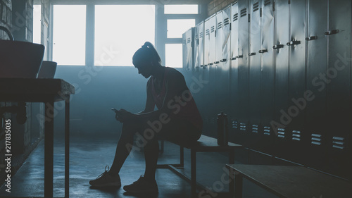 Caucasian female athlete preparing for a workout in a gym locker room, putting o Canvas Print