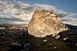 Eisbrocken vom Gletscher abgebrochen liegt am schwarzen Strand im Sonnen Gegenlicht