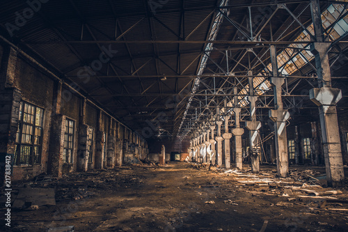 Abandoned and ruined dark industrial creepy warehouse inside with columns, corridor or tunnel view, old grunge factory building