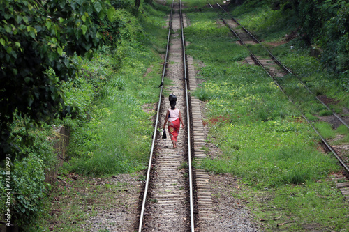 Fotografie, Tablou  Behind of Myanmarese lady villager walking on the railroad tracks and put the black bag or belongings on the head