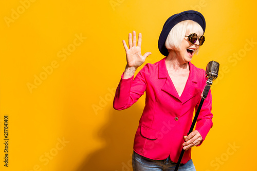 Fotografía  Portrait of charming modern grandmother holds up the microphone
