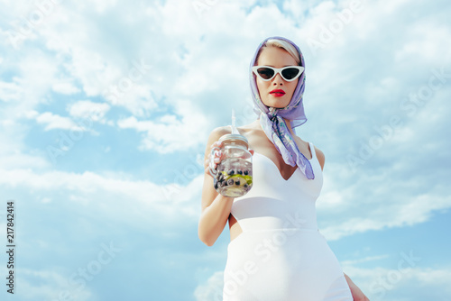 Fotografía fashionable girl in sunglasses and vintage swimsuit holding mason jar with fresh