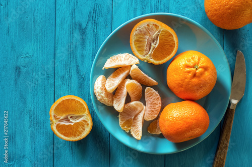 Ripe clementines with plate on rustic turquoise wooden table with copy space , top view