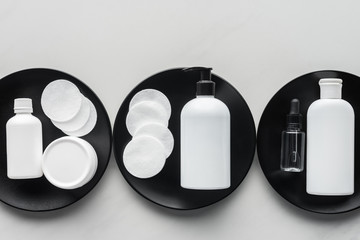 top view of bottles of cream and cosmetic pads on three black plates, beauty concept