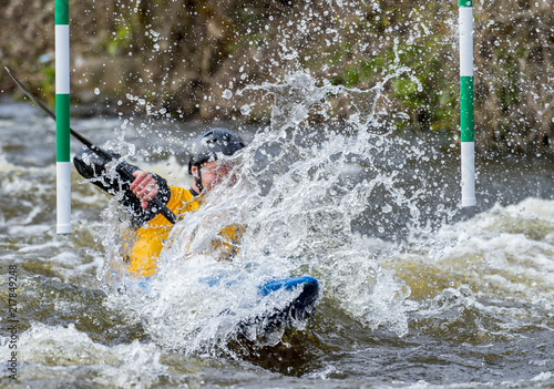 Photo  A canoeist paddling through fast running white water - about to go down a drop