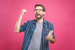 canvas print picture - I'm a winner! Happy man holding smartphone and celebrating his success over pink background.