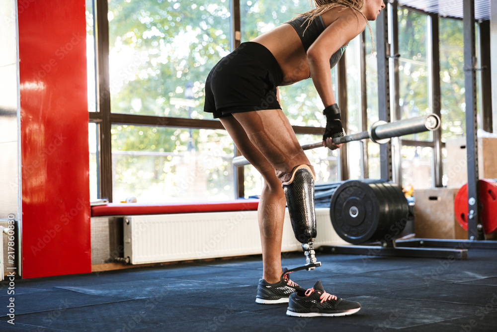 Fototapety, obrazy: Strong disabled sports woman make sport exercises with equipment in gym.