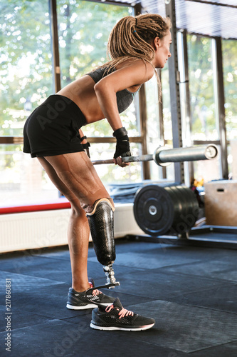 Photo Disabled sports woman make sport exercises with barbell equipment in gym