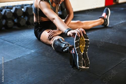 Disabled sports woman make sport stretching exercises in gym. Wallpaper Mural