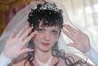 Bride in veil before the wedding. Brunette in a crown with pearls.