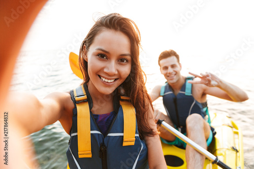 Fényképezés Loving couple kayaking on lake sea in boat make selfie by camera.