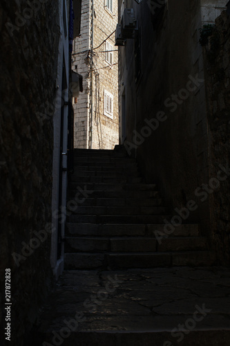 Fototapeten Schmale Gasse A dark alley in an old town with houses made from cobblestone