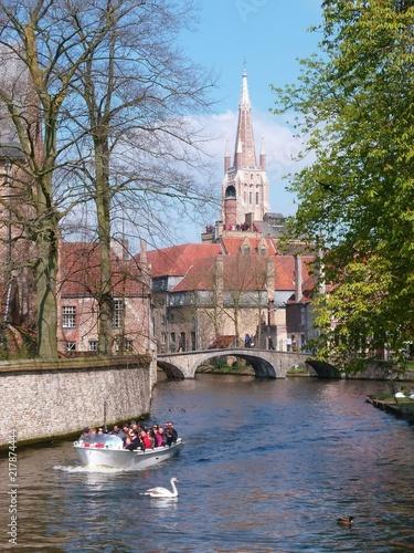 Keuken foto achterwand Brugge Bruges, promenade en barque sur un canal, avec vue sur le clocher de l'église Notre-Dame (Belgique)