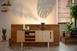 Candles on wooden cupboard in bedroom interior with plants and shadows on the wall. Real photo