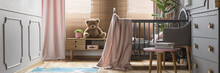 Panorama Of A Cozy, Gray Nursery Bedroom Interior With A Classic Wooden Baby Crib And Pastel Pink Decorations