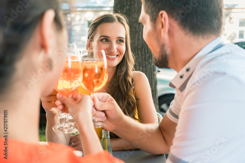 Leinwand Poster Beautiful woman and her best friends toasting with a refreshing alcoholic drink