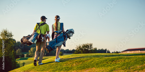 Foto Full length of a happy couple with a healthy lifestyle wearing golf outfits, whi