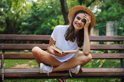 Obraz Cheerful young girl reading a book - fototapety do salonu