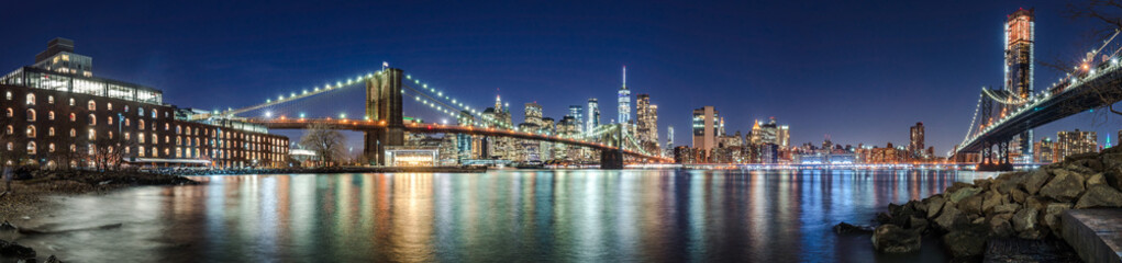 The skyscrapers of Lower Manhattan, the Brooklyn Bridge and the Manhattan Bridge in evening with the East River (panoramic). New York City