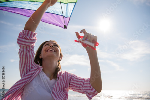 Photo Young Woman with kite at beach on autumn day